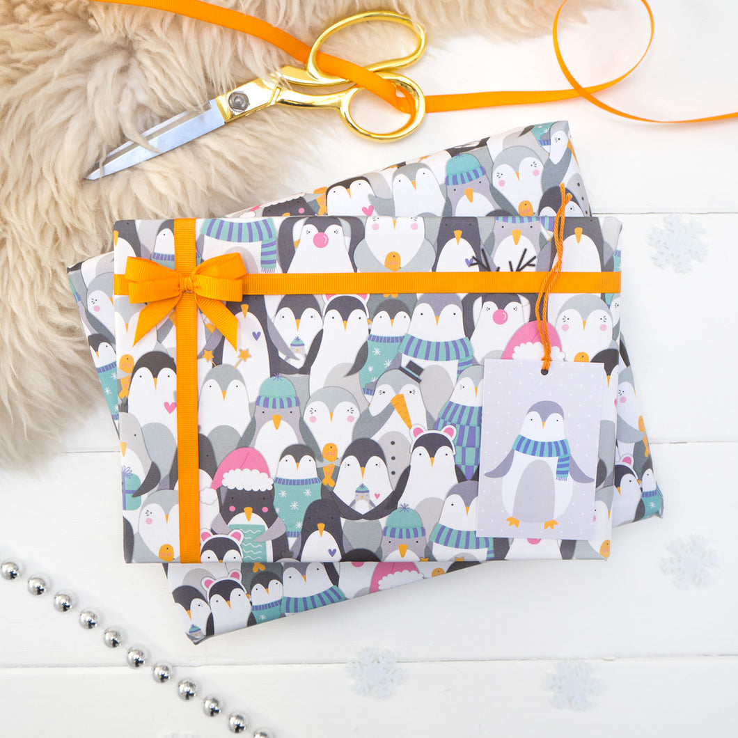 A parade of penguins wearing a variety of Christmas fancy dress printed onto white gift wrap. Matching penguin tag shown on the bottom right of the wrapping paper. The present is strung with orange ribbon and features a small bow.