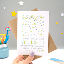 Load image into Gallery viewer, A personalised graduation card designed and made by Joanne Hawker in her somerset studio being held against a kraft brown envelope over a grey background with yellow and white stars. The confetti illustration and text is in varying tones of grey, blue and green.