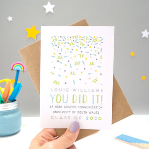 A personalised graduation card designed and made by Joanne Hawker in her somerset studio being held against a kraft brown envelope over a grey background with yellow and white stars. The confetti illustration and text is in varying tones of grey, blue and green.