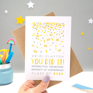A personalised graduation card designed and made by Joanne Hawker in her somerset studio being held against a kraft brown envelope over a grey background with yellow and white stars. The confetti illustration and text is in varying tones of grey, yellow and orange.