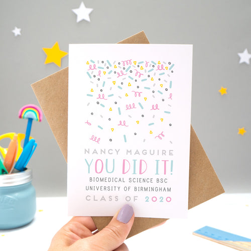 A personalised graduation card designed and made by Joanne Hawker in her somerset studio being held against a kraft brown envelope over a grey background with yellow and white stars. The confetti illustration and text is in varying tones of grey, blue and pink.
