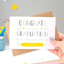 Load image into Gallery viewer, This personalised graduation card reads 'congrats on your graduation so proud of you [insert name].' The card is being held by Joanne Hawker in her somerset studio against a grey background with a kraft brown envelope with yellow and white stars. The card features grey text with varying tones of green, blue and yellow.
