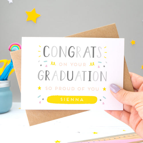 This personalised graduation card reads 'congrats on your graduation so proud of you [insert name].' The card is being held by Joanne Hawker in her somerset studio against a grey background with a kraft brown envelope with yellow and white stars. The card features grey text with varying tones of pink, blue and yellow.
