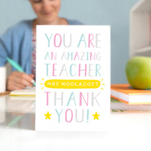 A personalised thank you teacher card that reads 'you are an amazing teacher [insert name of teacher] thank you! In pink, blue, grey and a pop of yellow
