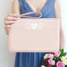 Load image into Gallery viewer, A pink, personalised Bridesmaids wristlet held by Joanne Hawker in a lilac bridesmaid dress with a bunch of pink and red roses.