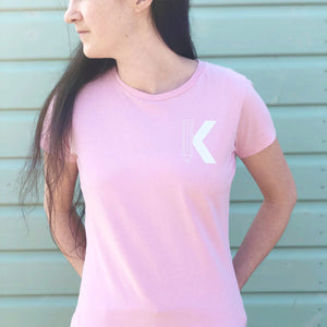 Pink tshirt with a white letter pencil initial K, modelled by Joanne Hawker in front of a green beach hut.