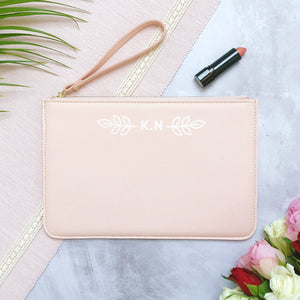 A pink personalised initial bridesmaid wristlet flatlay featuring the pouches lying on a grey background with lipstick, foliage and flowers used as props.