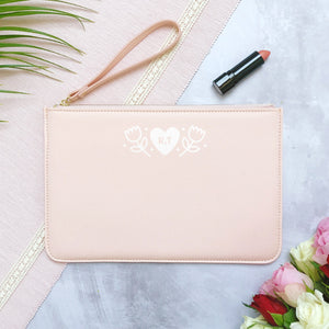 A pink personalised initial bridesmaid wristlet flat lay featuring the pouches lying on a grey background with lipstick, foliage and flowers used as props.