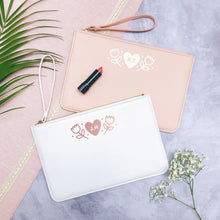Load image into Gallery viewer, A white and pink personalised initial bridesmaid wristlet flat lay featuring the pouches lying on a grey background with lipstick, foliage and flowers used as props.