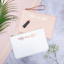 Load image into Gallery viewer, A white and pink personalised initial bridesmaid wristlet flatlay featuring the pouches lying on a grey background with lipstick, foliage and flowers used as props.