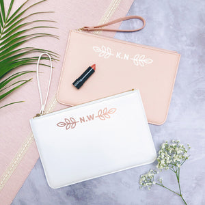 A white and pink personalised initial bridesmaid wristlet flatlay featuring the pouches lying on a grey background with lipstick, foliage and flowers used as props.