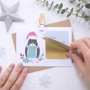 Personalised Penguin secret message Christmas scratch card with the scratch and reveal panel being applied.