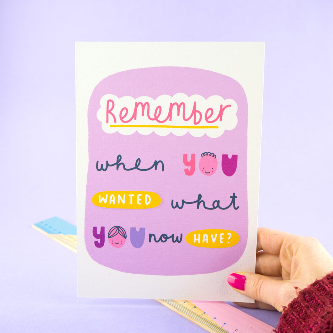 'Remember when you wanted what you now have?' a simple A5 print to help remember to appreciate what we have in life. The print is held in my right hand against a lilac background and above a ruler.