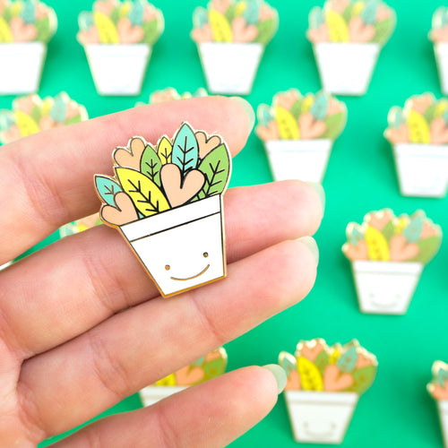 Heart plant enamel pin in a happy plant pot with hand for scale