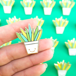 Aloe Vera Hard Enamel Pin in a happy plant pot, hand for scale