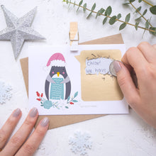 Load image into Gallery viewer, Personalised Penguin secret message Christmas scratch card being scratched off with a coin.