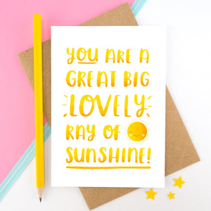 A yellow hand lettered love and friendship card featuring the words 'you are a great big lovely ray of sunshine'.