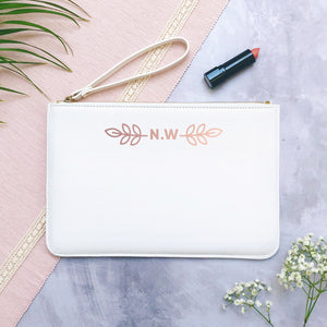A white personalised initial bridesmaid wristlet flatlay featuring the pouches lying on a grey background with lipstick, foliage and flowers used as props.