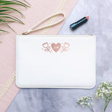 Load image into Gallery viewer, A white personalised initial bridesmaid wristlet flat lay featuring the pouches lying on a grey background with lipstick, foliage and flowers used as props.