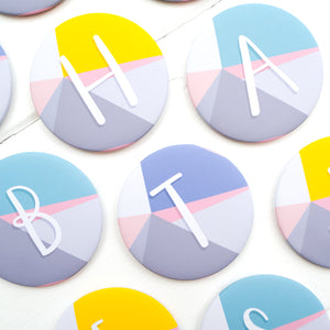 A selection of teal, purple and yellow, initial, monogram pocket mirrors.