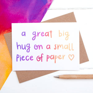 A great big hug on a small piece of paper, sympathy card flatlay.
