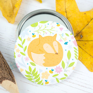 A sleeping, bright orange fox surrounded by flowers pocket mirror