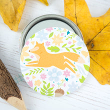 A bright orange jumping fox surrounded by flowers pocket mirror