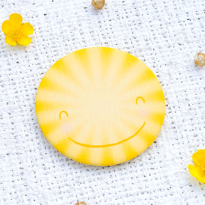 A bright yellow, happy sun, pocket mirror.
