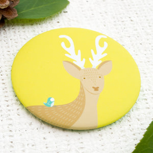 An illustrated deer with a blue bird on it's back pocket mirror.