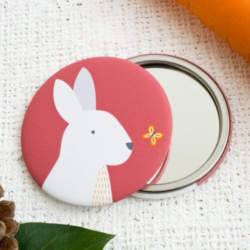 A white rabbit, on a red background, printed onto a compact pocket mirror.