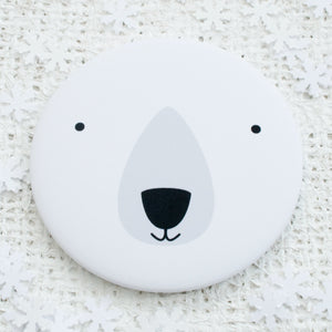 A pocket mirror with the face of a polar bear.