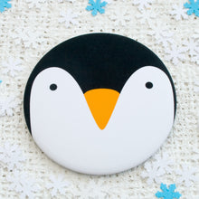 A pocket mirror with the face of a penguin