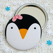 A pocket mirror with the face of a penguin wearing a pink bow.