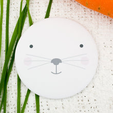 A pocket mirror with the face of a white rabbit.