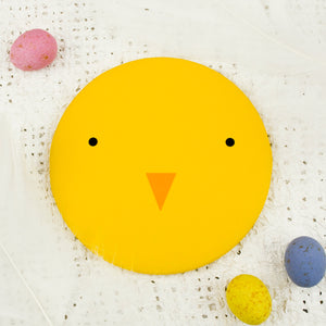 A bright yellow pocket mirror with the face of a chick.