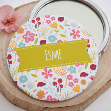 A personalised pocket mirror with flowers, lady birds and a space to add a name of your choosing.