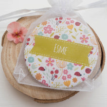 The pocket mirror packaged in a white organza bag.