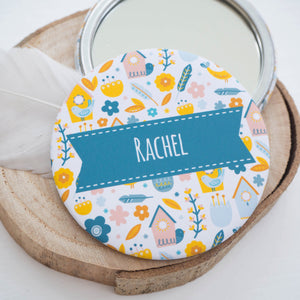 A personalised pocket mirror with a range of illustrated birds and their houses in blue and yellow.
