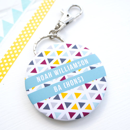 Personalised graduation bottle opener key ring with a geometric pattern and space for a name and degree classification