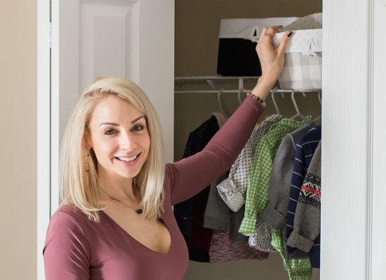mom reaching for decorative storage basket in baby's closet