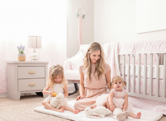 beautiful mom and two daughters enjoying time together in pink nursery