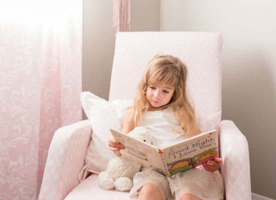 young girl sitting in nursery chair reading a story book