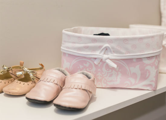 soft pink storage basket with pretty little baby girl shoes