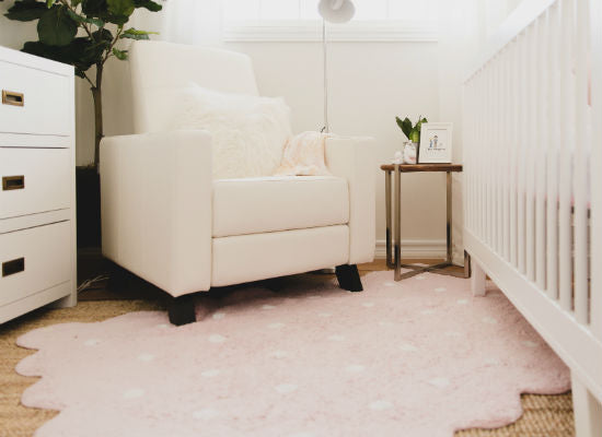 soft pink rug on hardwood floor in front of baby crib in nursery