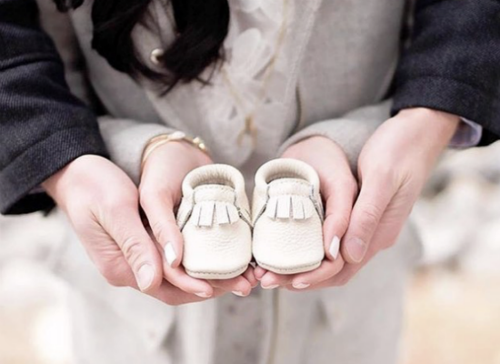 expecting parents holding baby shoes in their hands