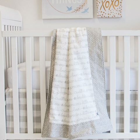 white crib with neutral crib baby blanket with hand written script