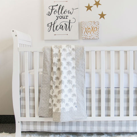 white crib with soft grey elephant and pebble baby blanket, and plaid crib skirt
