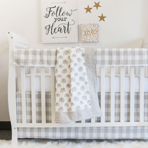 white crib with neural soft grey elephant, pebble and plaid crib set and follow your heart artwork