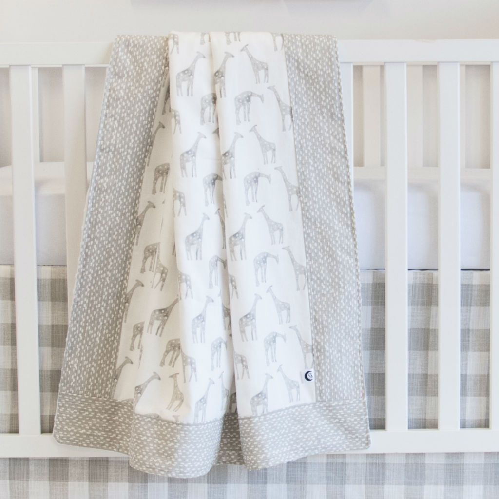white crib with soft grey giraffe and pebble baby blanket, and plaid crib skirt