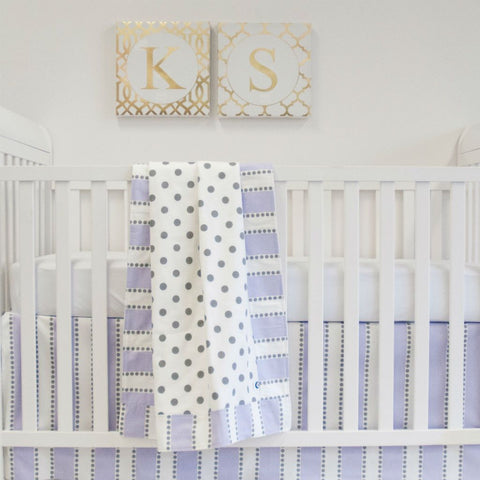 white crib with grey polka dot blanket and lilac trim and lilac stripe crib skirt